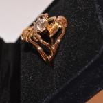 Voici une bague or rose vue de profile, faite d'un entrelacs de petites feuilles avec au centre de la canopée un diamant en solitaire.