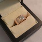 Voici une bague en or rose avec en solitaire un diamant taille princesse.