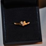 Voici une bague en or rose avec un petit cœur et en son centre un diamant sertit de trois grains.