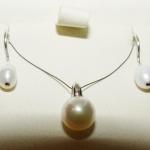 Une parure, boucles d'oreilles col de cygne et pendentif, les perles sont montées avec de l'or blanc.