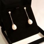 Voici une paire de boucles d'oreilles or blanc, diamants et perles.