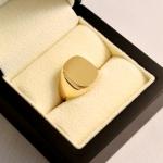 """Une chevalière en or jaune de forme """"coussin"""" avec pour simple décors un brossé."""