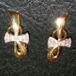 Paire de boucles d'oreilles en or jaune avec le nœud en or blanc et diamants.