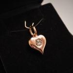 Voici un cœur charnu en or rose avec un diamant en son centre.
