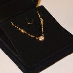 Voici un collier en or jaune à trois diamants serti en serti clos.