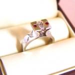 Bague en or blanc, surmontée d'un diamant de taille marquise, entourée de 2 rubis. Les flancs sont rehaussés de deux diamants de taille brillant.