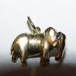 Petit éléphant en or jaune avec des spinelles synthétiques bleus pour faire les yeux.