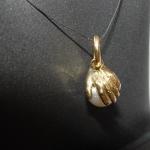 Main en or jaune posée sur une perle.