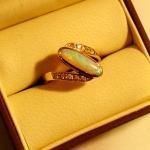 Bague or jaune avec une opale en solitaire épaulée de diamants. Pièce réalisée à partir d'anciens bijoux qui n'étaient plus appréciés.
