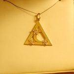 Triangle or jaune avec une petite lune en son centre saupoudré d'étoiles avec diamants.