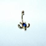 Piercing de nombril représentant une tortue marine en or jaune avec un saphir bleu.