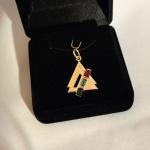 Ici nous avons le pendentif et la bague assortie. Tous deux en or jaune sertis d'un rubis, d'une émeraude et d'un saphir bleu.