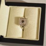 Voici une bague en or blanc avec un diamant noir en son centre entouré de petits diamants blanc.