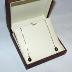 Boucles d'oreilles en or blanc avec col de signe et perles noires en forme de goute.