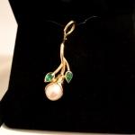 Voici un pendentif en or jaune avec une perle de forme poire, pour bourgeon et des émeraudes pour feuilles.