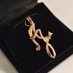Pendentif en or jaune au lettre A et J (Les initiales des prénoms du couple) entrelacées autour d'un petit diamant.
