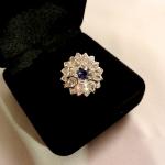 Voici une bague en forme de petite fleur en or blanc au pétale de diamants et au cœur de saphir.