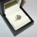 Une rose des vents en or blanc avec un petit diamant en son centre.