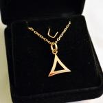 Un pendentif en or jaune, un triangle courbe.