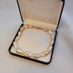 Voici une collier de perles baroques avec un mousqueton or jaune.