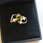 Voici une bague or blanc à petites feuilles de lierres avec, en solitaire, une tourmaline verte.