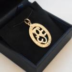 Voici deux pendentifs en or jaune fait d'initials découpées gravé de dates en chiffre romain tout autour.