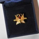 Voici une bague papillon en or jaune avec deux petit diamant dans les ailes, un rubis en forme de cœur au centre, gravée de deux initials et flanqué de deux petit symboles infini. l'or et les diamant on été récupéré sur une ancienne chevalière.