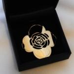 Voici la silhouette d'une rose découpé dans de l'or jaune. C'est la partie métallique d'un bracelet, elle viendra s'attacher au poignet au moyen d'un ruban par les deux trous percés latéralement.