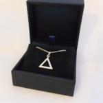 Un pendentif en argent, un triangle droit et sa chaine.