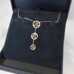 Voici un collier en argent où les 3 cercles forment le nom Maud, le symbole astrologique du lion remplaçant le A.