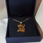 Voici un pendentif or jaune avec un petit diamant dans la bélière fait aux initials des amours du client.