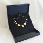 Voici un collier or jaune fait de petites étoiles, lunes et soleils gravés dans les cercles.